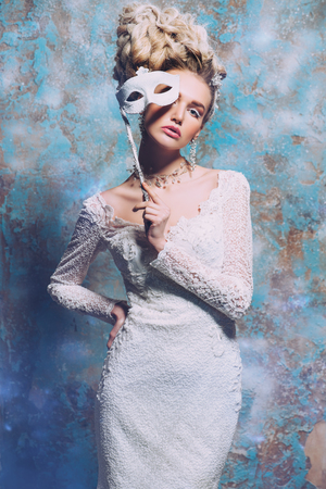 A portrait of a cold beautiful lady wearing a tight dress with a mask. Beauty,cosmetics, hairstyle, fashion. Stock Photo