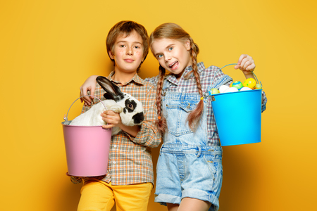 Happy children are posing with Easter attributes on yellow  background. Happy childhood. Easter decorations.