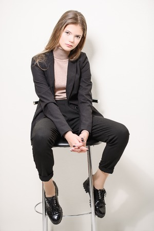 A pretty teenage girl is sitting on a barstool. Beauty, fashion. Standard-Bild - 115319934