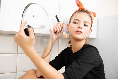 An attractive young girl with a headband is posing sitting  on the kitchen set. Pin-up style. Beauty.