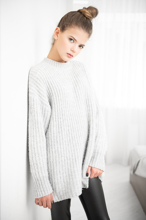 Portrait of a cute girl teenager in large knitted sweater at the room. Beauty, fashion. Foto de archivo
