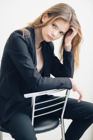 A pretty teenage girl is sitting on a barstool. Beauty, fashion. Standard-Bild - 115321338