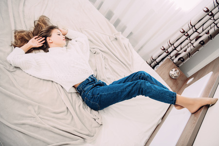 Portrait of a cute girl teenager lying on the bed in the bedroom. Beauty, fashion. 免版税图像