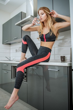 Portrait of a beautiful sexy girl in jogging suit with a glass of water at the kitchen in home. Fitness at home. Beauty, fashion. 版權商用圖片