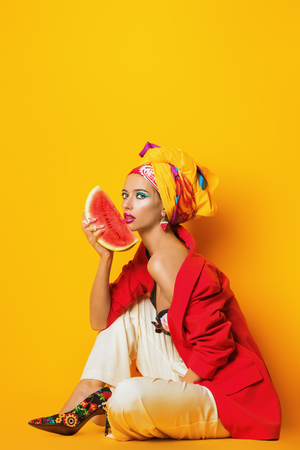 Portrait of a fashionable woman with bright make-up. Yellow background. Beauty, fashion, make-up concept.