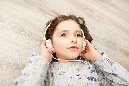 A pretty little girl is lying with headphones on the floor. Fashion home shot. Childhood. Kids fashion.
