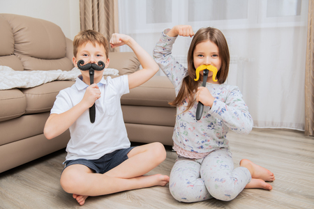 Cute girl and boy are having fun and playing games at home. Childhood. Kid's fashion Stok Fotoğraf