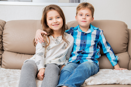 Leuke jongen en meisje zitten knuffelen op de bank. Mode huis schot. Jeugd. Kindermode.