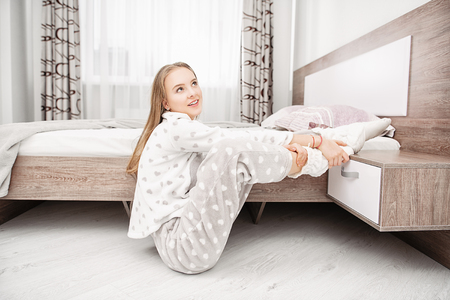 An attractive young girl is posing in a pajamas sitting on the floor near the bed at home. Beauty, cosmetics.