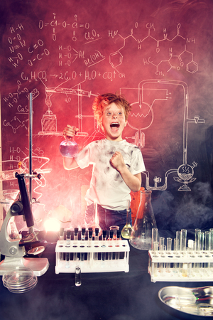 Funny schoolboy doing experiments in the laboratory. Explosion in the laboratory. Science and education. Banco de Imagens