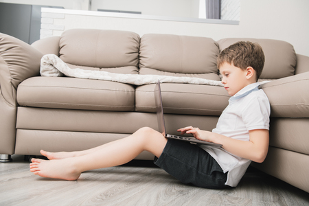 A cute boy is lying with laptop on the floor and smiling at camera. Childhood. Kid's fashion.