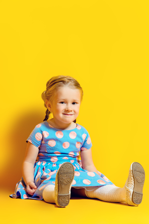 A full length portrait of a positive young pretty girl sitting on the floor. Summer bright fashion for kids.