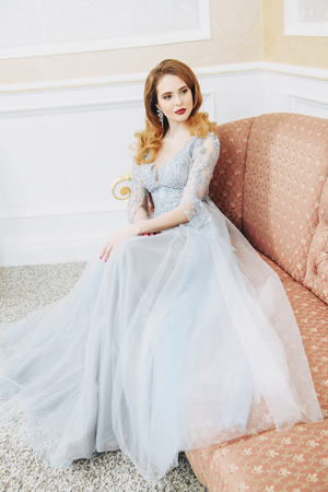 A portrait of a beautiful elegant woman in the wedding dress on the couch. Fashion, wedding dress.