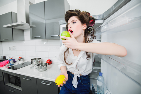 An attractive girl in everyday clothes and curlers is tasting fruit in the kitchen. Cooking in the kitchen. Gastronomic concept. Фото со стока - 115684019