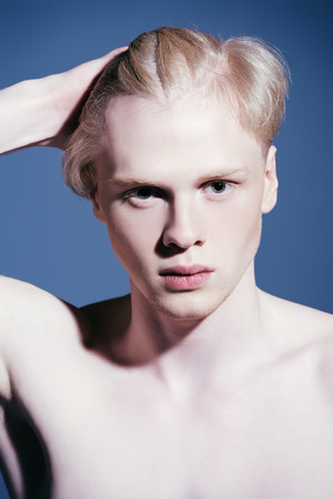 Portrait of a shirtless young man with blond hair posing at studio. Men's beauty and health.