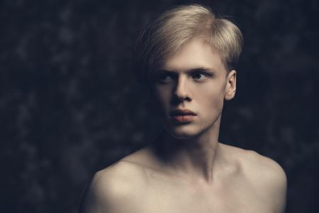Porträt eines hemdlosen jungen Mannes mit blondem Haar, das im Studio aufwirft. Grauer Hintergrund. Männer Gesundheit.