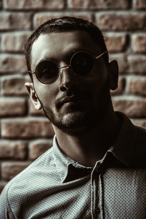 Close-up portrait of a handsome brunet man in sunglasses over brick wall background. Men's beauty, fashion. Men's barbershop, Hairstyle.