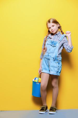 Moda infantil. Linda niña de nueve años con largo cabello rubio posando en ropa de verano con un balde de huevos de Pascua. Tiro del estudio. Retrato de cuerpo entero.
