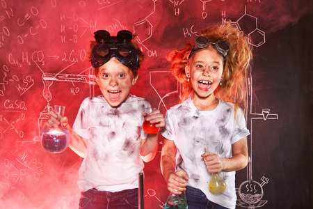 Funny school children doing experiments in the laboratory. Explosion in the laboratory. Science and education.