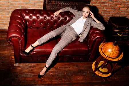 Sexy relaxed woman in a elegant suit posing in luxurious vintage interior. Full length portrait. Beauty, fashion. Imagens