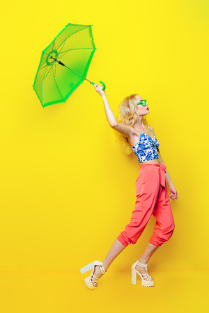 Attractive young woman wearing bright clothes and glasses with umbrella over yellow background. Bright style, fashion. Optics style.