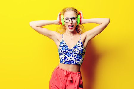 Attractive young woman sings a song in bright headphones, wearing bright clothes and sunglasses over yellow background. Bright style, fashion. Optics style. Stock Photo