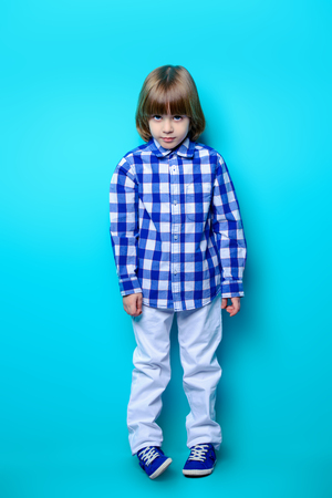 A cute six-year-old boy poses in checkered shirt and white jeans with  smartphone in hand over blue background. Childrens fashion. Studio shot.