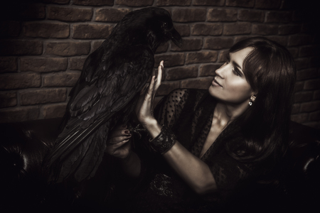 A portrait of a femme fatale in dark clothes posing on a leather sofa on a brick wall background with a black raven.