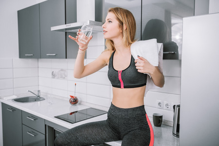 A portrait of a beautiful sexy girl in jogging suit in the kitchen at home. Fitness at home. Beauty, fashion.