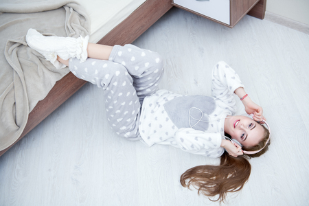 Portrait of an attractive young girl lying in a pajamas with headphones and smartphone on the floor near the bed at home. Beauty, cosmetics.