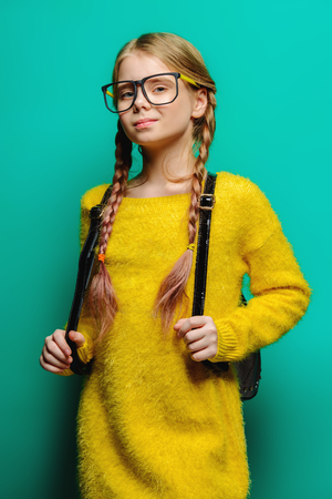 Cute nine year old girl posing in studio in fluffy yellow dress over turquoise background. Children's beauty and fashion.
