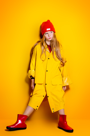 A bright fashionable girl in a raincoat and a hat. Spring fashion for kids.