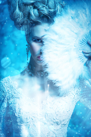 A close up portrait of a cold beautiful lady with a fan posing in the studio over the blue background. Beauty,cosmetics, hairstyle.