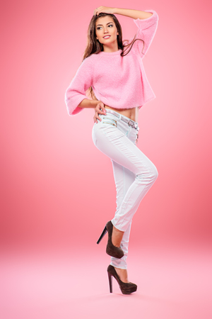 A beautiful and cute young lady posing over pink background. Fashion concept.