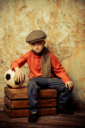 A full length portrait of a young boy with a soccer ball. Fashion, beauty.