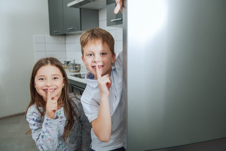 Two cute kids hiding behind the fridge in the kitchen. Childhood. Kid's fashion.