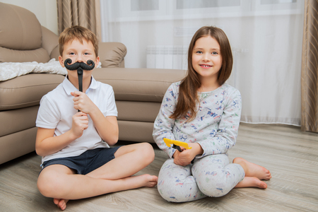 Cute girl and boy are having fun and playing games at home. Childhood. Kid's fashion Imagens
