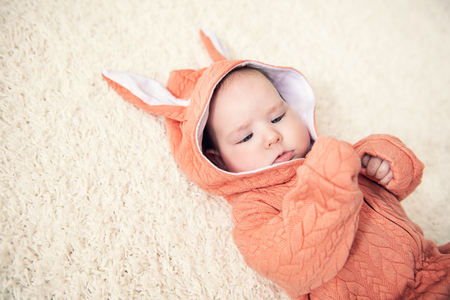A portrait of a funny baby wearing a jumsuit of a hare. Family, parenthood. Goods for newborns. Stock Photo
