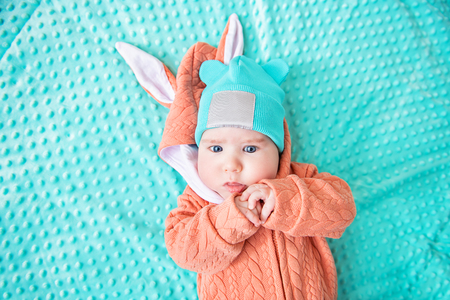 A close-up portrait of a funny baby wearing a hat and a jumsuit of a hare. Family, parenthood. Goods for newborns.