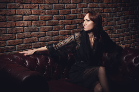 A portrait of a femme fatale in dark clothes posing on a leather sofa on a brick wall background. Stock Photo
