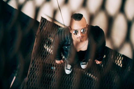 Portrait of a punk guy on the stairs through the lattice. Guy in the backyard. Fashion, subculture.