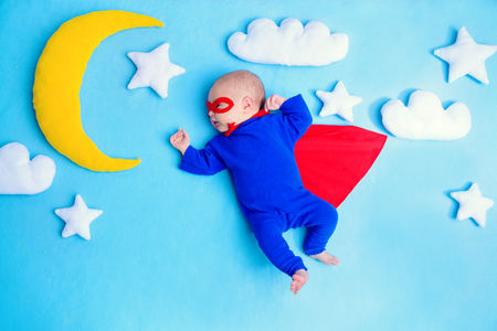 Little baby superhero with red cape flies through the night sky. Children in thematic costumes.