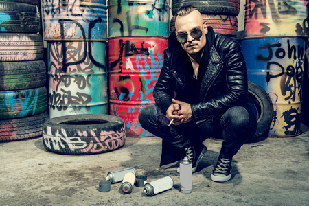 Portrait of a punk man with the spray paint on the street. Guy in the backyard. Fashion, subculture. Stockfoto