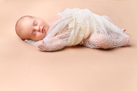 Portrait d'un joli bébé nouveau-né endormi enveloppé dans une couverture tricotée. Soins bébé, soins de santé.