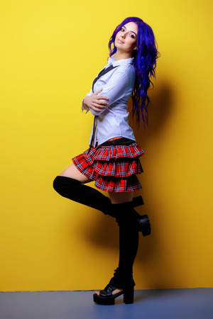 Portrait of a student girl with purple hair in white blouse and checkered skirt posing on yellow background at studio. Japanese style anime. Stock fotó