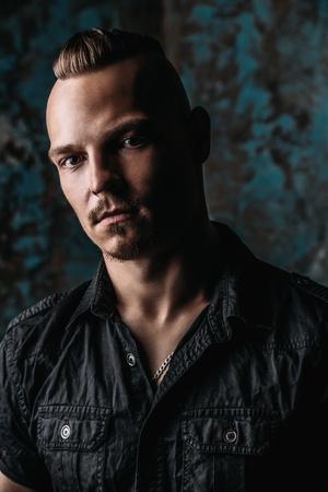 Portrait of a punk man in black shirt on grunge background. Fashion, subculture. Studio shot.