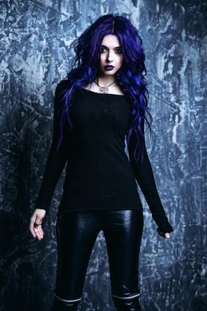 Attraktive junge Frau mit lila Haaren in einer schwarzen Sweatshirt-Lederhose und Plateauschuhen. Schönheit, Jugendmode. Haare färben. Kosmetik, Make-up. Standard-Bild