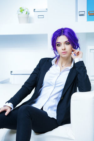 Elegant businesswoman with purple hair and elegant suit at the office. Contemporary business.