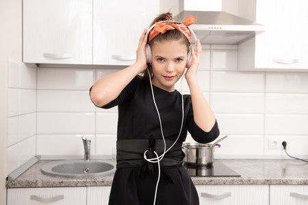 An attractive young girl is posing with a headband on the kitchen. Pin-up style. Listening to music.