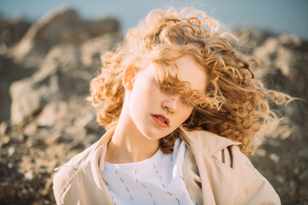 A portrait of a charming young girl with curly fair hair in fashionable clothes. Fashion, beauty.